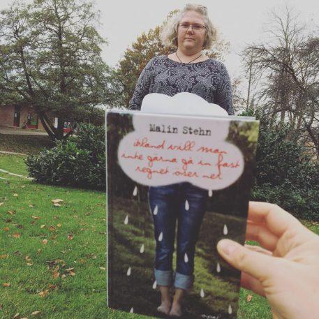 """En kvinna håller upp boken """"Ibland vill man inte gärna gå in fast regnet öser ner"""""""